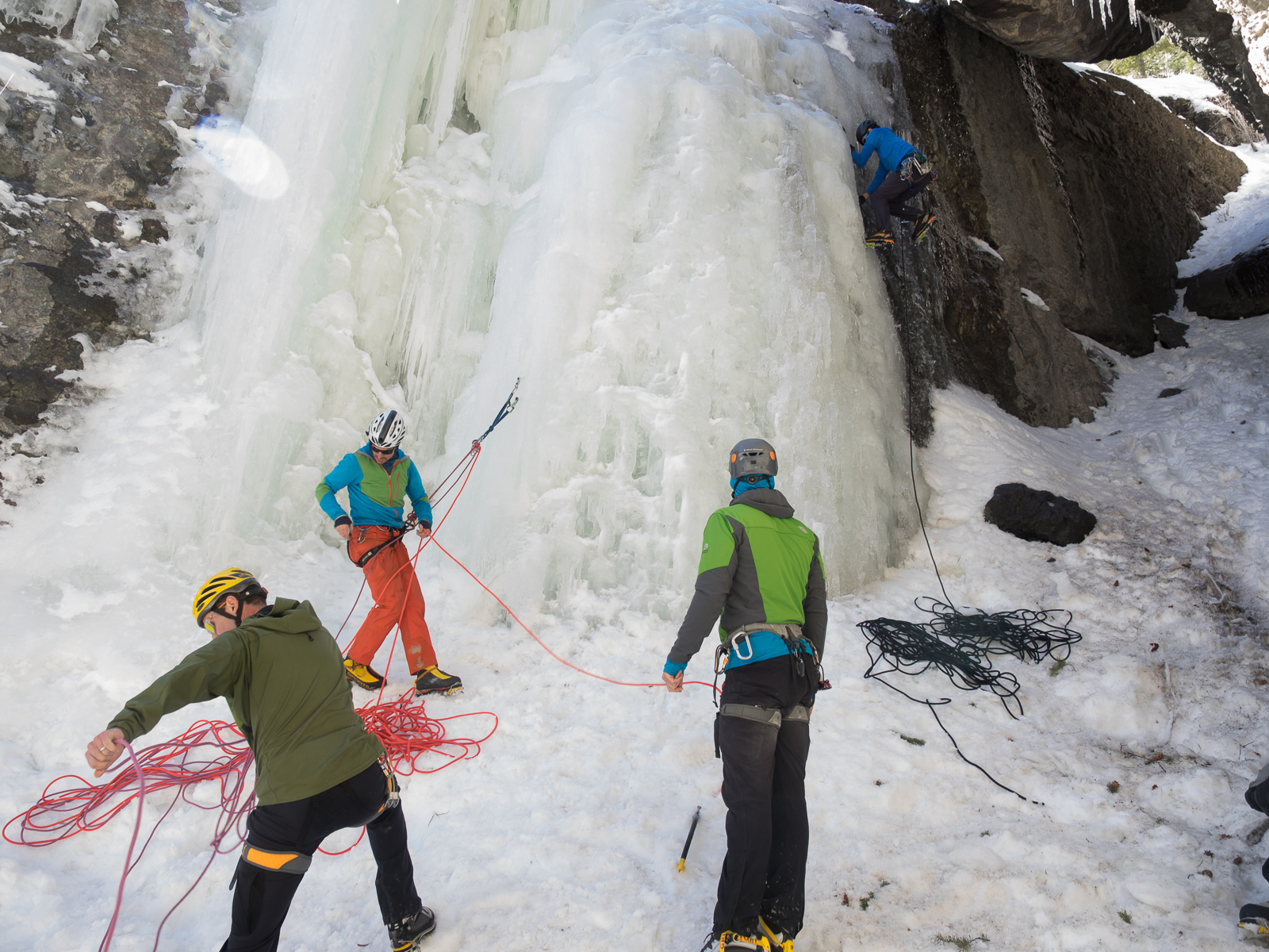 Steve House instructing on belay changeovers, while Vince Anderson heads up the ice to set up a top rope.